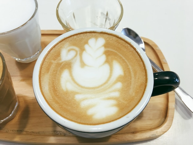 Café caliente dibujando un corazón en una taza azul sobre textura de madera.