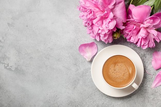 Café caliente y flores de peonía rosa