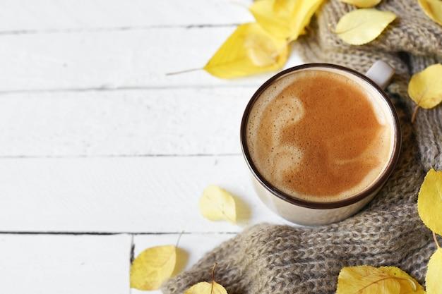 Café caliente y hojas de otoño sobre fondo blanco de madera