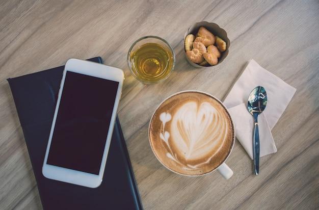 Café caliente del latte del arte en una taza en la tabla de madera en fondo de la falta de definición de la cafetería.