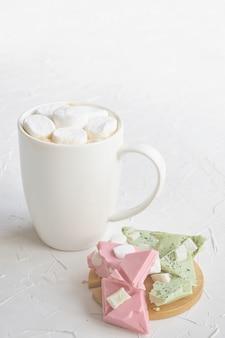 Café caliente con malvaviscos en una taza blanca junto a chocolate con limón y fresa en la mesa