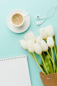 Café caliente de la mañana con flores de tulipanes y auriculares