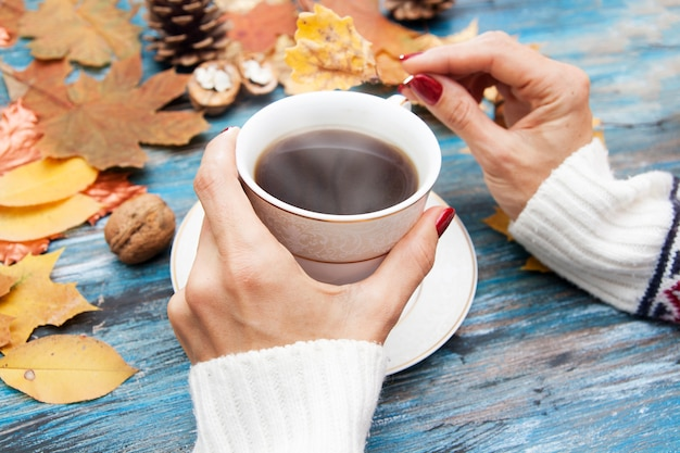 Café caliente en manos de una niña, hojas de otoño, un suéter de punto sobre un fondo azul mesa vintage. acogedor ambiente otoñal en octubre, noviembre