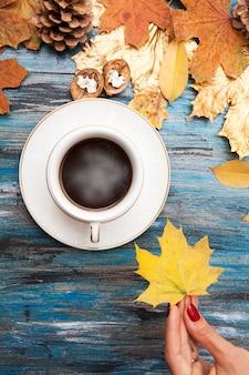 Café caliente en una mesa de madera, en la mano de una niña - otoño hoja de arce amarilla