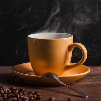 Café caliente en taza con cuchara en plato