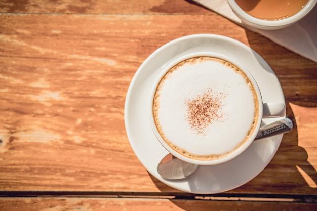 Café caliente y té caliente colocados en la mesa de madera temprano en la mañana con copyspace