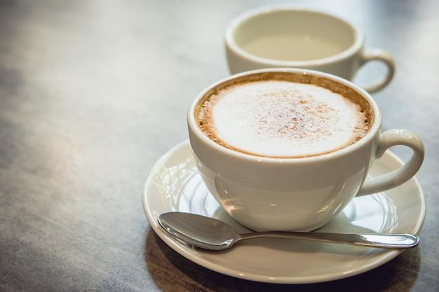 Café caliente y té caliente colocados en la mesa de mármol temprano en la mañana con copyspace