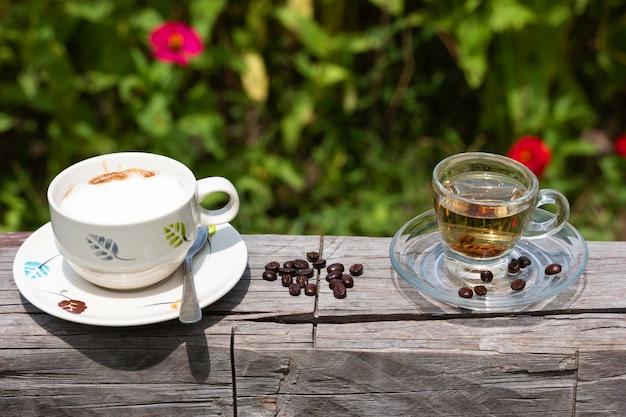 Café caliente en un vaso en la madera en el jardín de flores