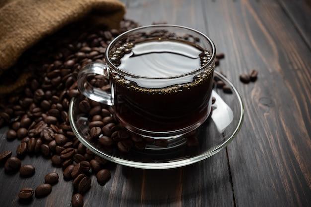 Café caliente en un vaso sobre la mesa de madera.