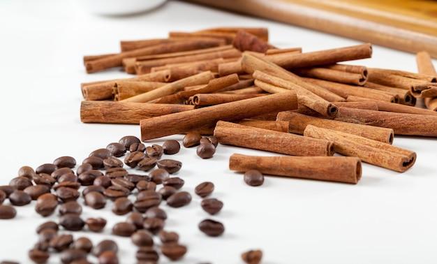 Café y canela, granos de café aromáticos reales y canela aromática en la mesa, granos de café para beber café