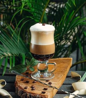 Café en capas con crema y granos de café sobre tabla de madera rústica