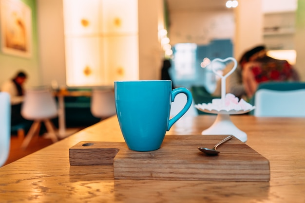 Café capuchino caliente en cafetería en mesa de madera