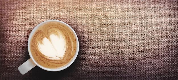 Café capuchino caliente con forma de corazón tardío en la taza de café, sirva en ratán marrón con tamaño de pancarta