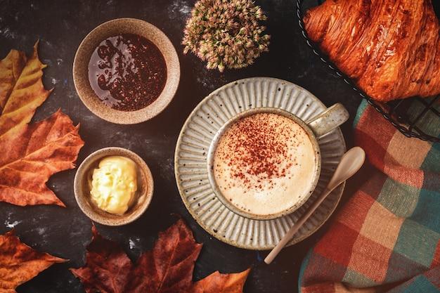 Café capuchino con croissant en la mesa, concepto de desayuno de otoño, vista superior