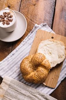 Café con capuchino y rebanada de pan con queso en una tabla de cortar sobre la mesa