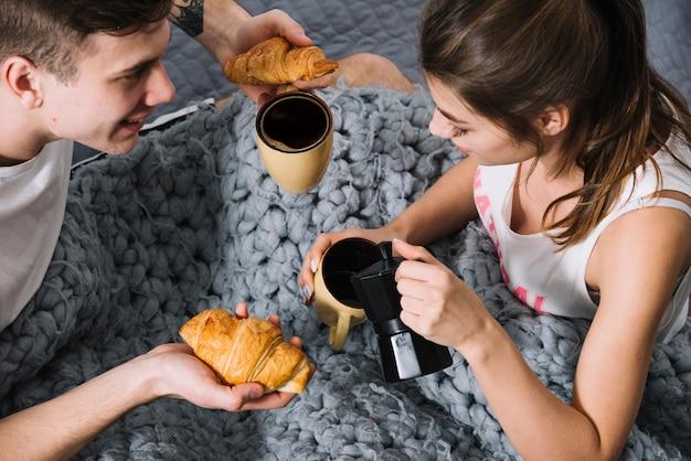Café de colada de la mujer en taza en cama