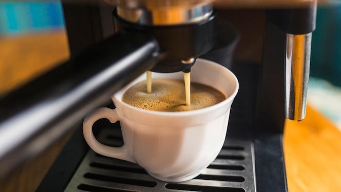 Café con espuma vertiendo desde la máquina de café espresso
