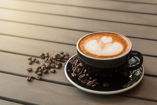 Café con leche caliente con arte latte en una taza negra sobre la mesa.