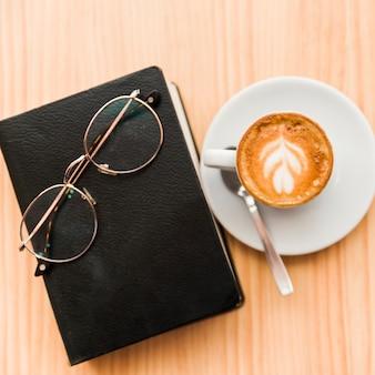 Café con leche fresca con gafas y libro sobre la mesa de madera