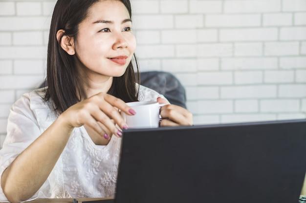Café de consumición asiático de la mujer de negocios en el lugar de trabajo