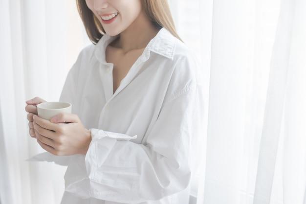 Café de consumición hermoso de la mujer joven que hace una pausa la ventana en la casa.