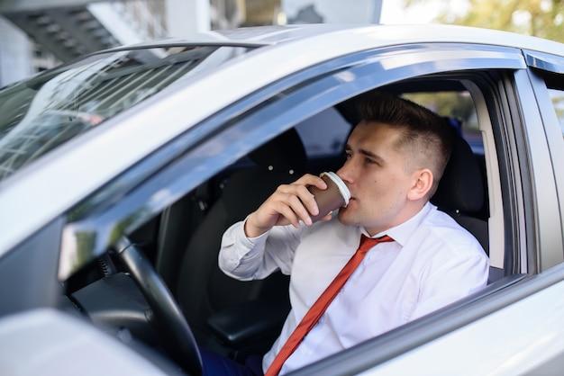 Café de consumición del hombre de negocios en el coche.