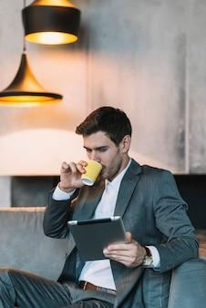 Café de consumición del hombre de negocios joven mientras que mira la tableta digital