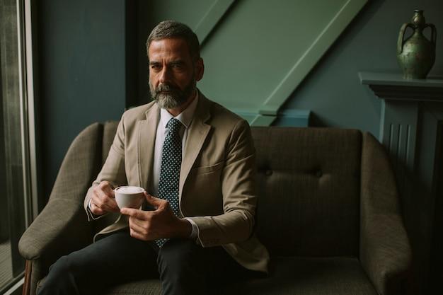 Café de consumición del hombre de negocios mayor hermoso en el pasillo