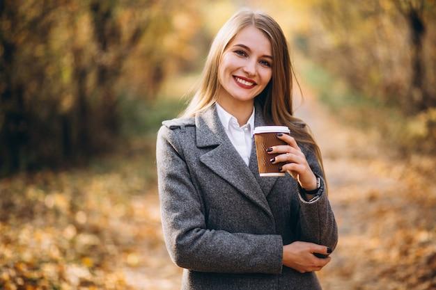 Café de consumición joven de la mujer de negocios al aire libre