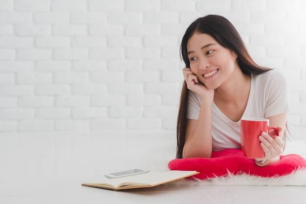 Café de consumición de la muchacha hermosa asiática y lea un libro en una almohada en casa.