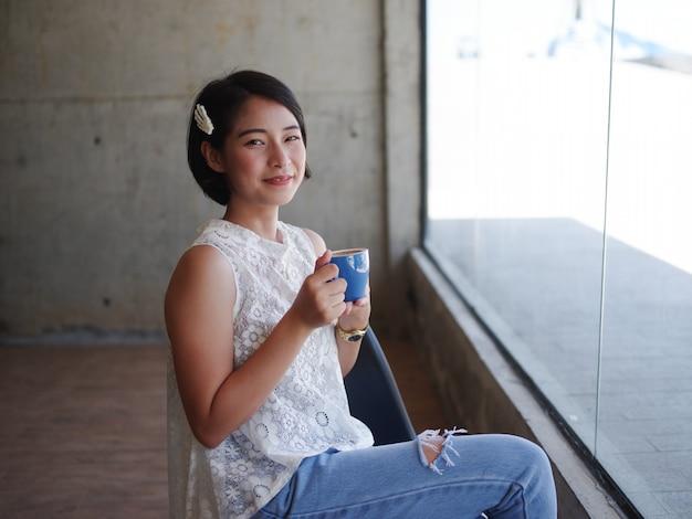 Café de consumición de la mujer asiática en café