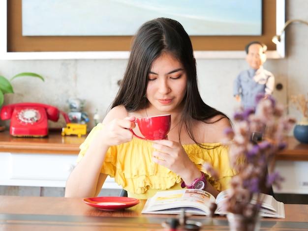 El café de consumición de la mujer asiática y se relaja en café de la cafetería
