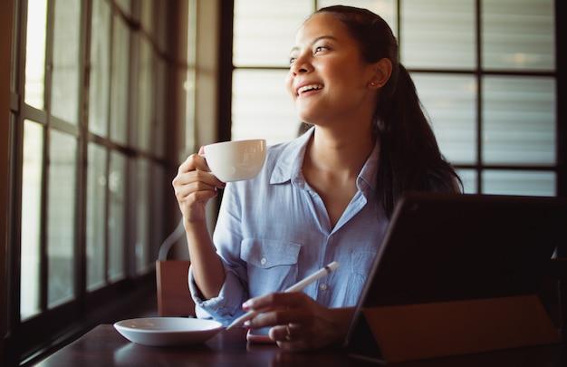 Café de consumición de la mujer asiática y trabajo con el ordenador portátil en café