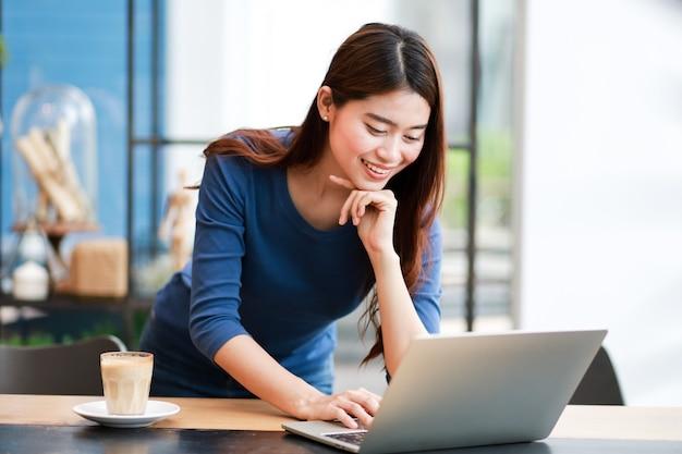 Café de consumición de la mujer asiática y trabajo con el ordenador portátil
