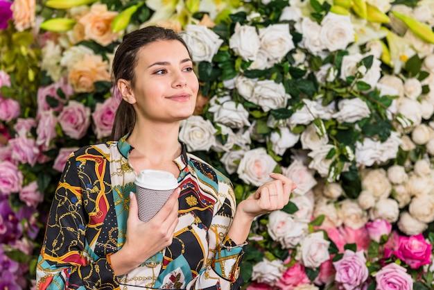 Café de consumición de la mujer bonita en casa verde