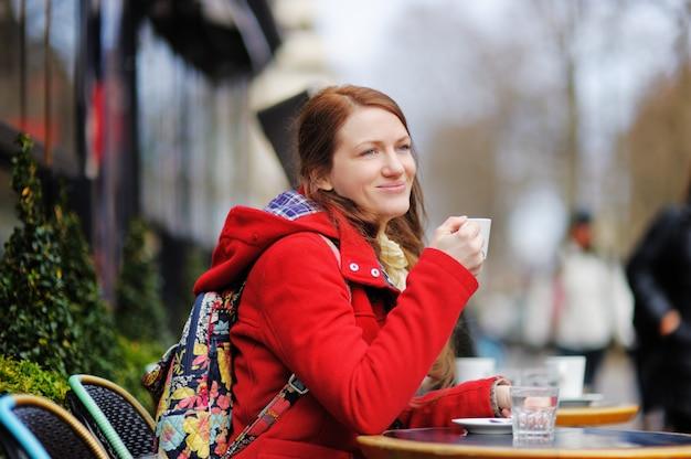 Café de consumición de la mujer joven en un café parisiense de la calle en el día de primavera