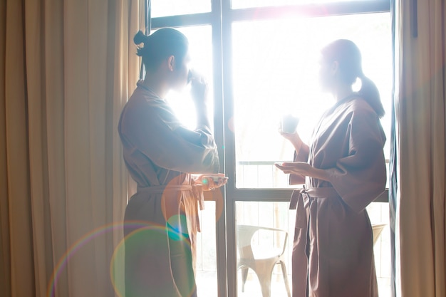 Café de consumición de los pares asiáticos y mirada fuera de ventana.