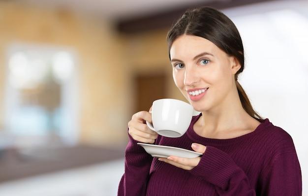 Café de consumición del retrato joven y hermoso de la mujer