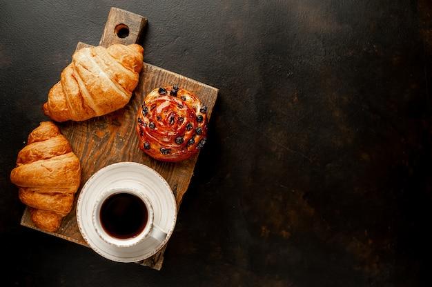 Café y croissant, bollo sobre una mesa de piedra. desayuno de la mañana, con copia espacio para texto