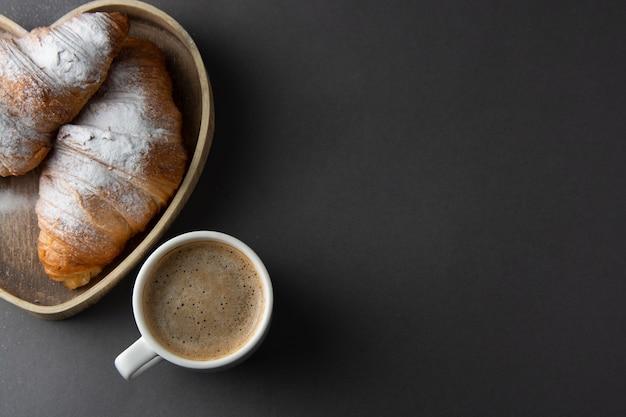 Café con croissant en caja de madera en forma de corazón. copia espacio