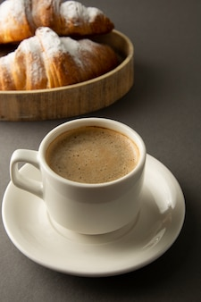 Café con croissant en la mesa de trabajo, desayuno en el trabajo.