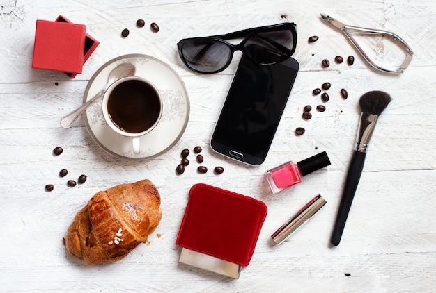 Café con croissant, teléfono celular, gafas de sol y herramientas de maquillaje sobre una mesa