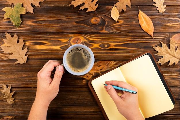Café y cuaderno sobre fondo de hojas de otoño