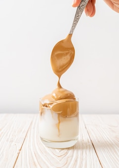 Café dalgona. bebida de tendencia batida cremosa y esponjosa helada con espuma de café y leche.