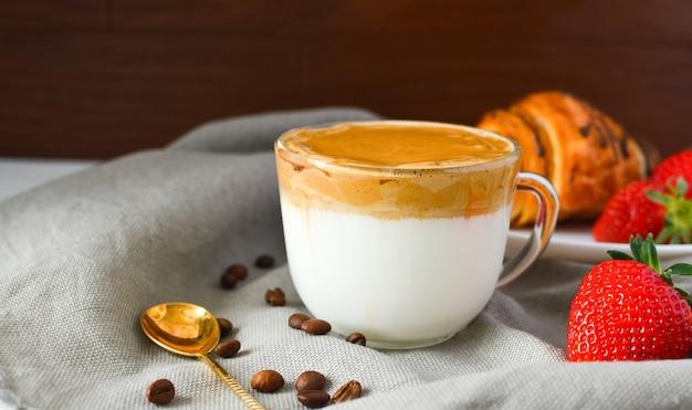 Café dalgona en una taza transparente, fresas, croissant sobre una superficie oscura. bebida de tendencia. cafe mañanero. desayuno saludable.