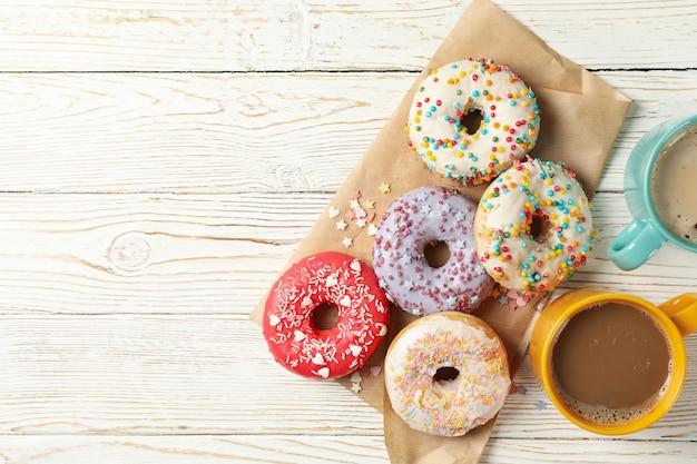 Café y deliciosos donuts sobre fondo de madera, vista superior