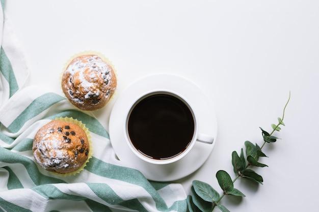 Café y dos muffins sobre fondo blanco.