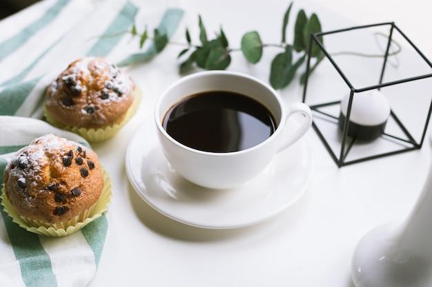 Café y dos muffins sobre superficie blanca