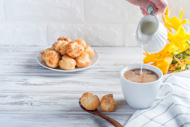 Café y eclairs sobre una mesa blanca.