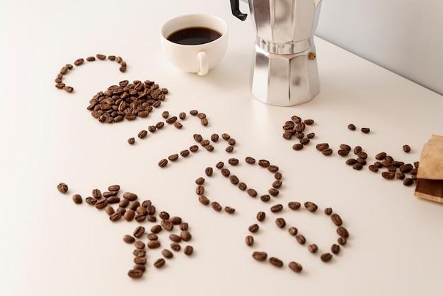 Café escrito con granos de café en la mesa blanca